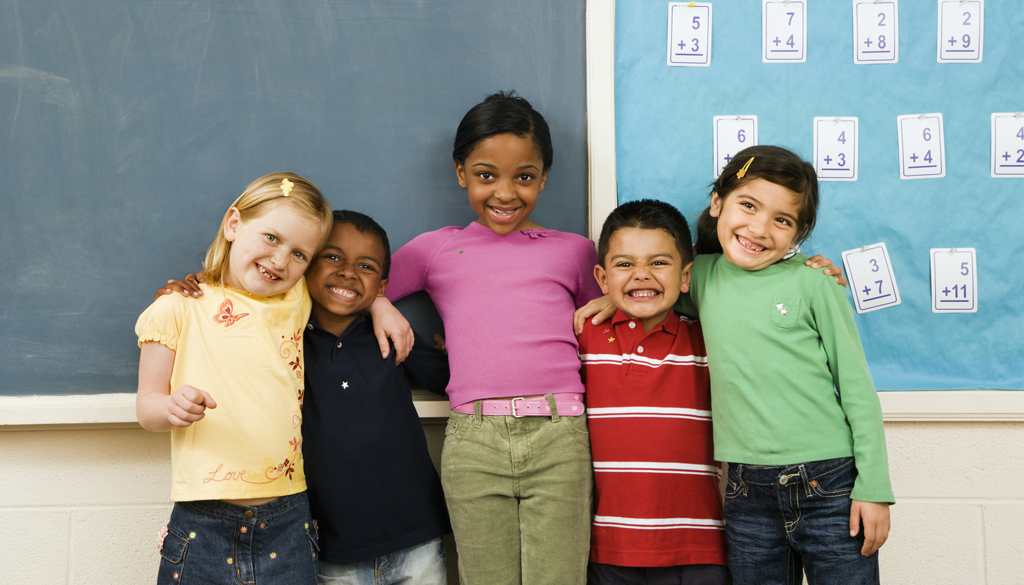 Ethnically diverse elementary school kids posing before a blackboard